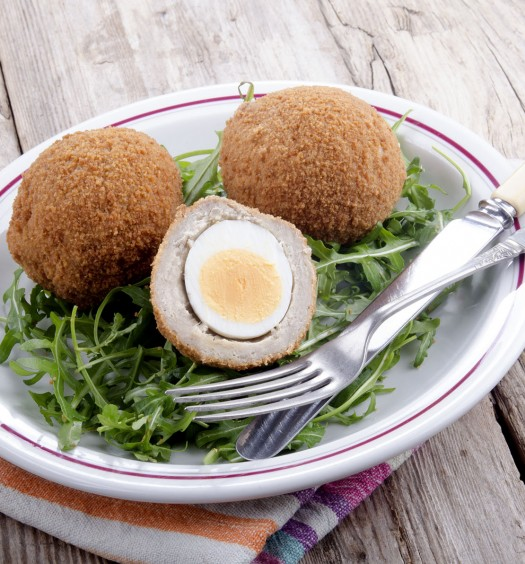 scotch eggs on a plate with rocket salad